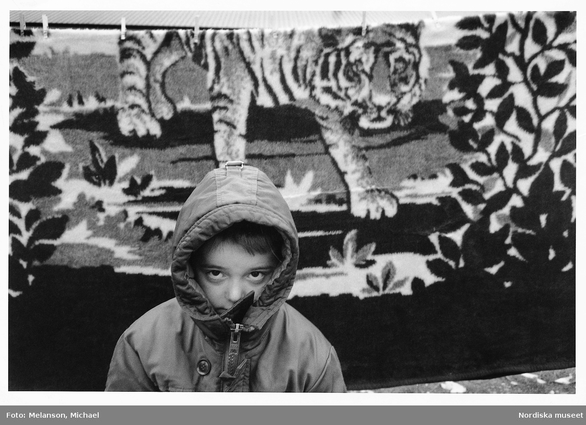 Pojke iförd jacka med kapuschongen uppfälld står framför en matta med motiv föreställande tiger i vegetation. På en flyktingförläggning i Ystad 1993.