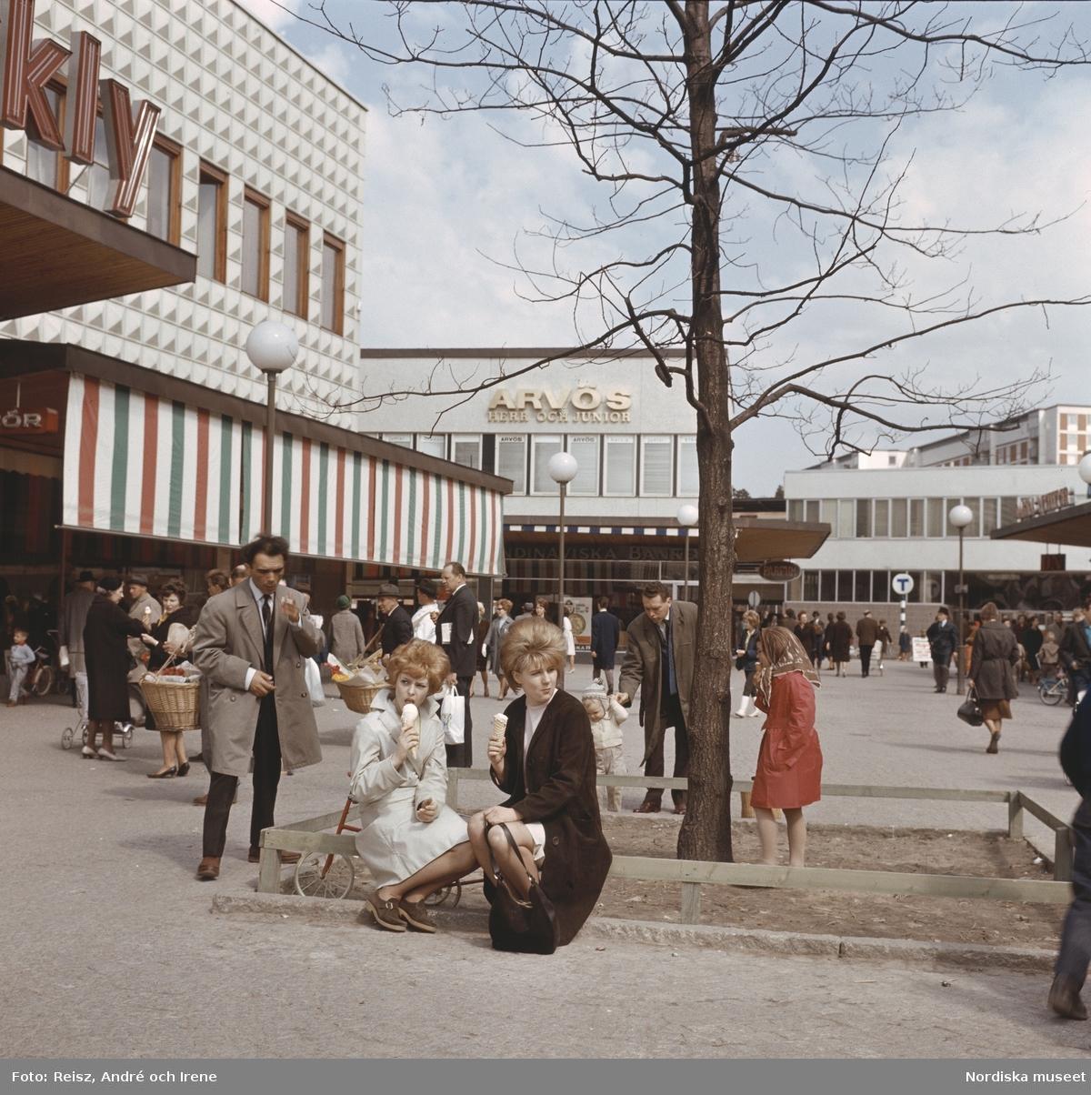 Förort, Farsta centrum. Folkliv runt torget, två kvinnor äter glass under ett träd.