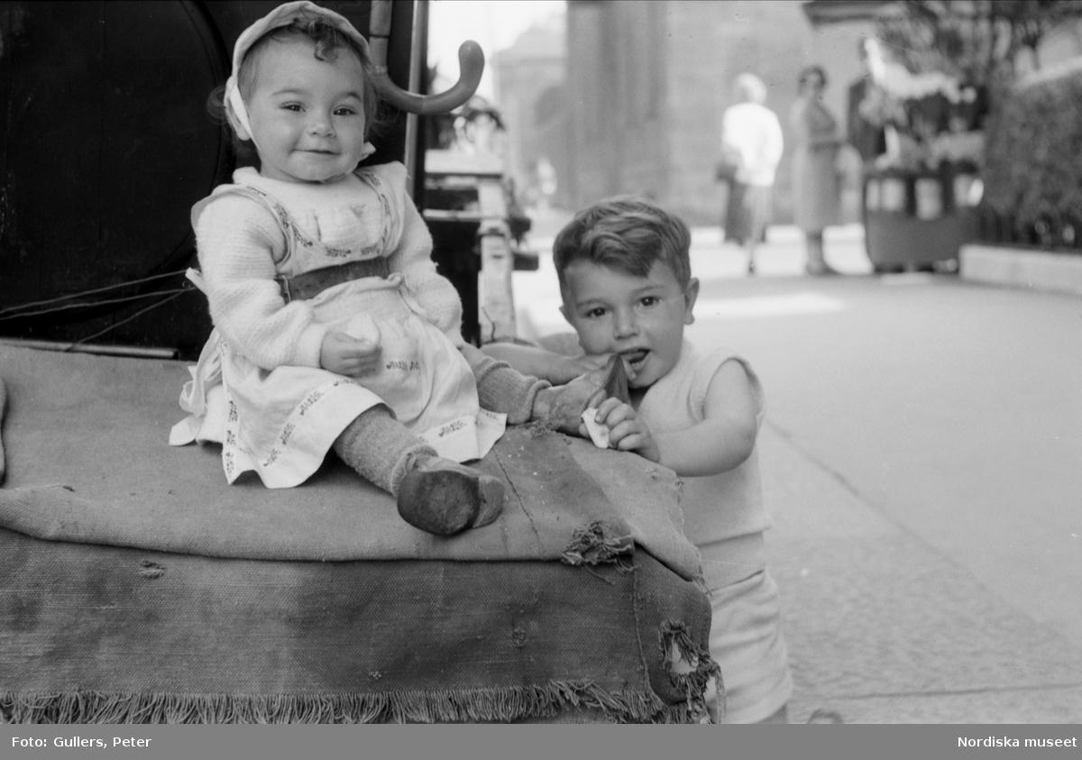 Liten flicka och pojke vid en kärra på gata. Italien.