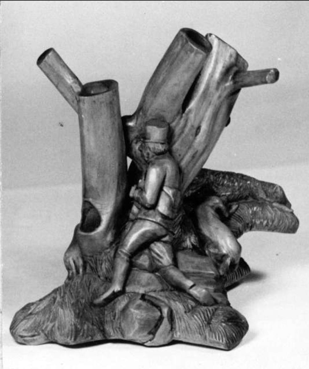 Pipställ av trärot, brunfernissat. Hål för fem pipor. Motiv: En jägare med hundar.