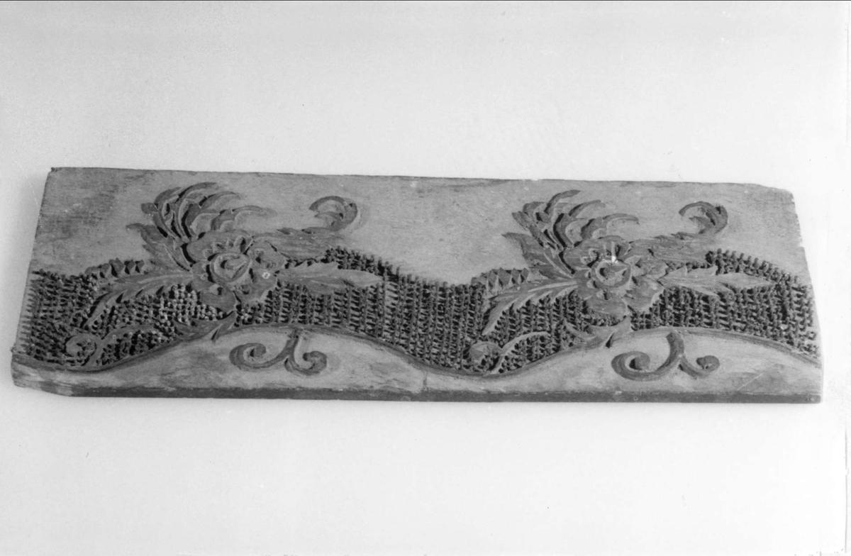 Tryckstock av trä för tapettryck. Motivet utgörs dels av två skurna blommor och blad dels av en mängd små mässingsstift placerade i ett vågformat band längs blommornas ena sida.