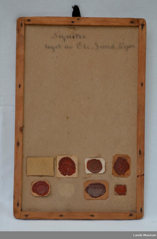 6 stk av O.Smeds lakksignetter montert på papplate med treramme. (Har opprinneleg vore 8 stk, 2 mangler)