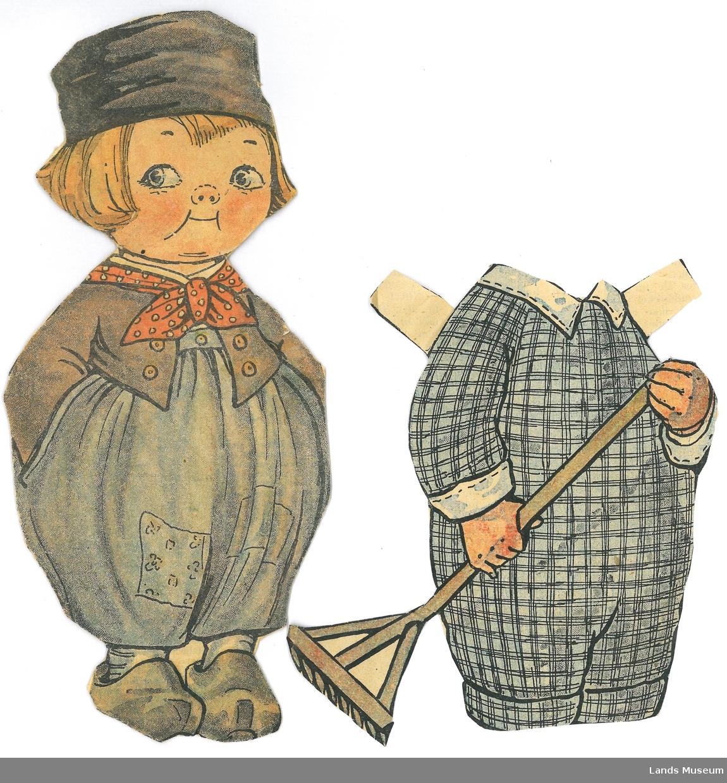 Papirdukke med klær som er klipt ut av avis/magasin. Dukken er montert på papp.  A- dukke, gutt med hollenderdrakt, tresko og lue, 19,5 x 8,5 cm B- rutete drakt med rive, 12,5 x 10 cm