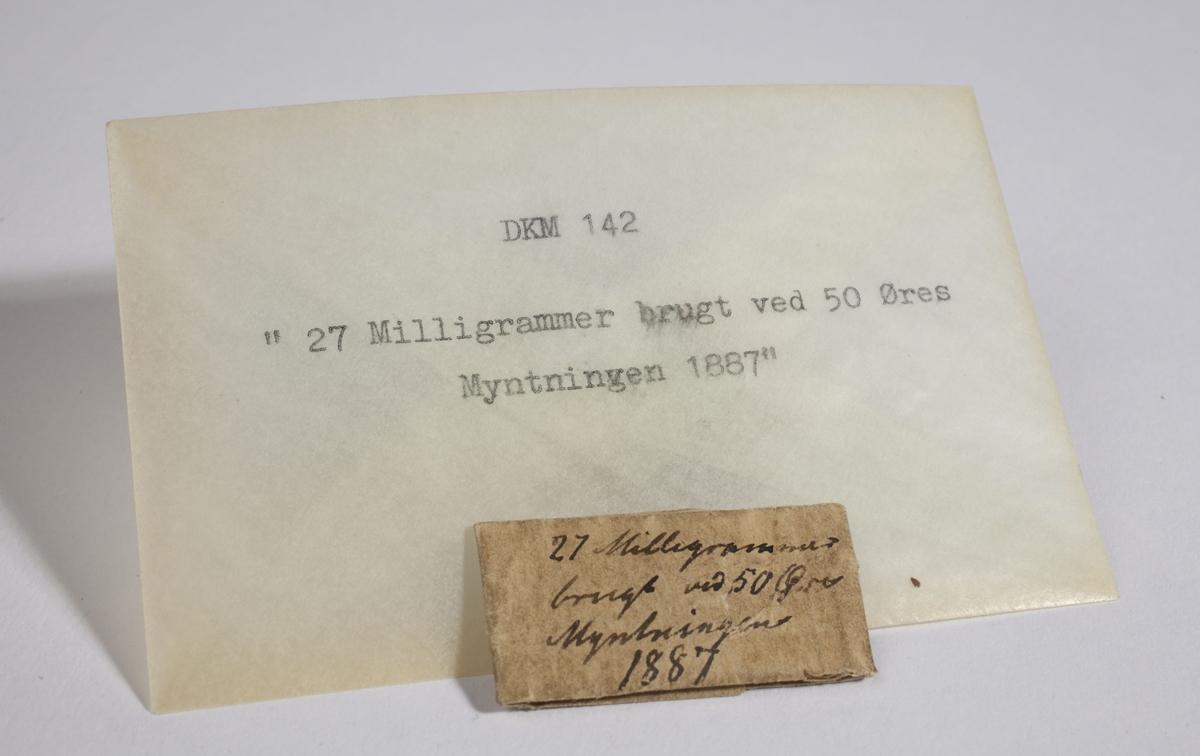 Papir brettet til en konvolutt som inneholder to små metallbiter.