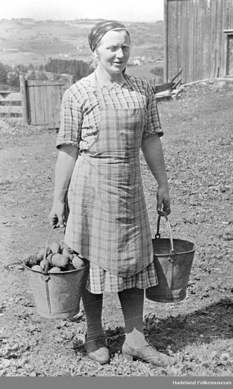 Elise Sandli bærer poteter i sinkbøtter. Hun har blåtøykjole med forkle over.