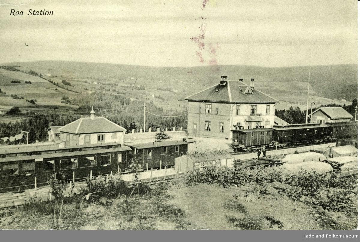 Roa jernbanestasjon fotografert fra vest med stasjonsbygninger. Godsvogner og passasjervogner på flere jernbanespor.