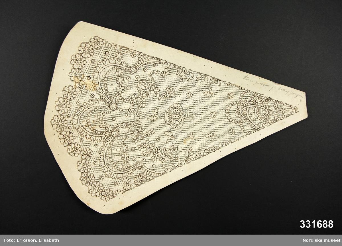 """Uppstucket knyppelmönster på styv  grå kartong, trekantigt till formen, spetsmönstret uppritat med svarta konturer och mönstret tätt prickat. Mönstertypen med blommor på en nätbotten typiskt för Vadstenaspetsar.  Mönstret utgör en sektion av ett parasoll (med 8 sektioner) och i mönstret är inkomponerat namnet Jozephine (sic!) under en kunglig krona. I kanten skrivet med blyerts: """"Till en parasoll för drottning Josehine"""". /Berit Eldvik 2012-11-08"""