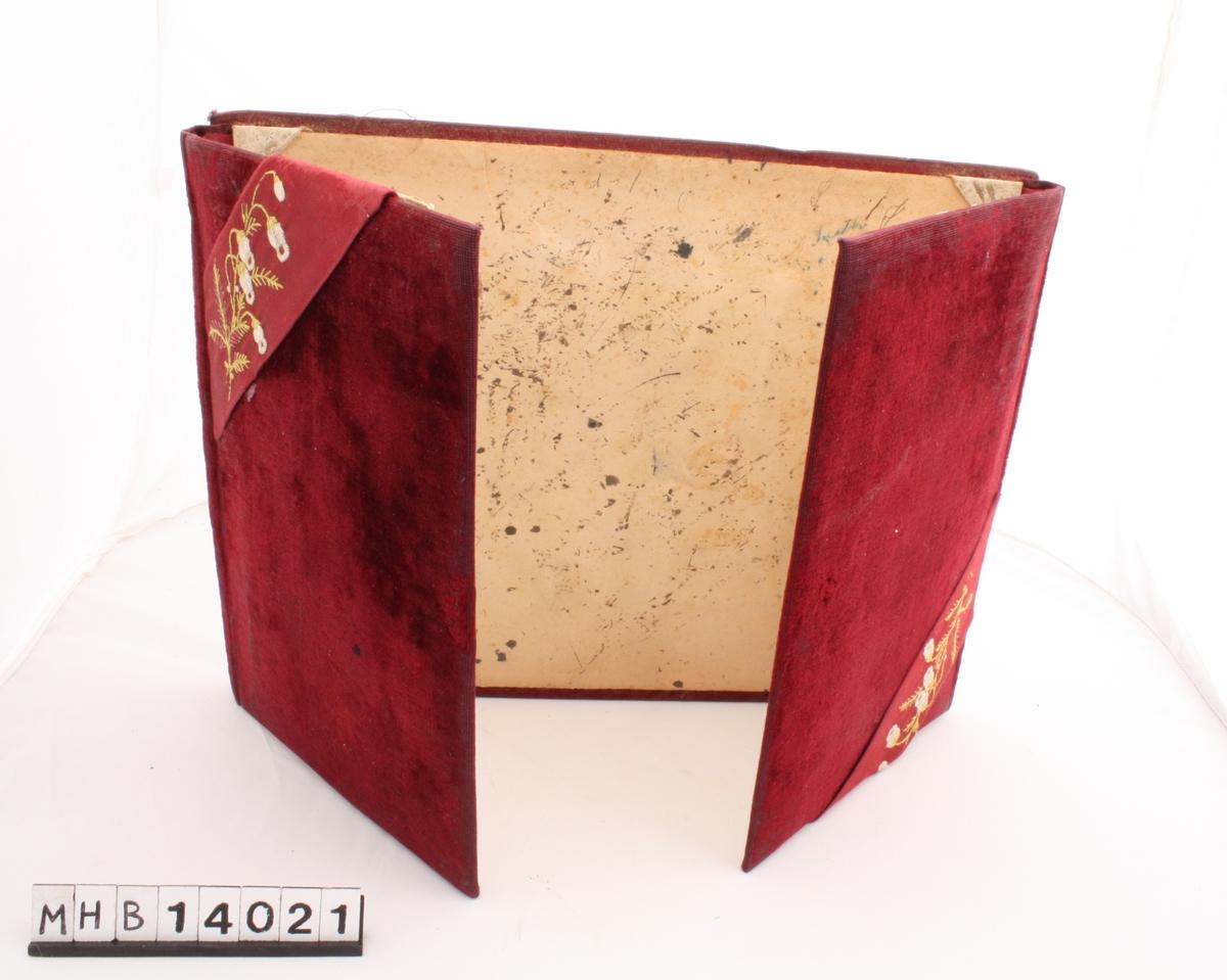 Mappe med plass til brevpapir og konvolutter. Den består av papp-plater trukket i burgunder plysjstoff. Baksiden består av en rektangulær plate som i kortsidene er festet til to mindre, rektangulære plater som foldes over baksiden slik at de danner mappens forside. To bånd med broderte blomster går skrått over to motstående hjørner på mappens forside.