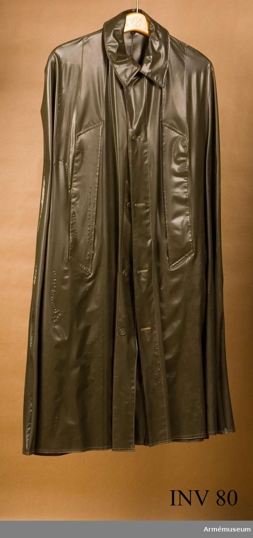 Av gråbrungrön gummiväv. Nedvikt krage. Knäpps med 5 knappar framtill. Ärmöppning framtill. Har tillhört Gustav VI Adolf (1882-1973).