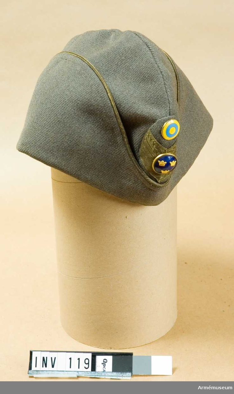 """Av gråbrungrön diagonal. Sidenfoder. Initialerna """"G A"""" i  mössan. Gul passpoal runt kanten på uppslaget Fram en  blåemaljerad knapp med tre kronor m/1865 plus ett blått och  gult nationalitetsmärke m/1941. Generalsgalon."""