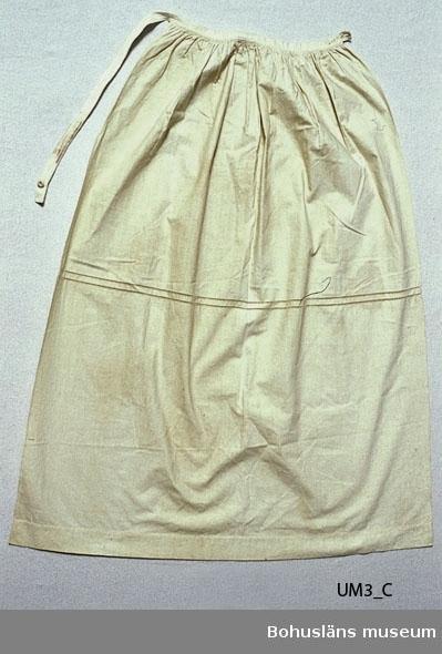 """Vitt förkläde (gulnat) av linnetyg?, av en rektangulär tygbit, rynkad upptill mot en smal linning. Linningen går utanför tyget en liten bit i höger sida. Där finns ett knapphål. På vänster sida bildar linningens fortsättning en lång  knäpptamp som lägges runt midjan baktill och knäpps med en sydd knapp  i knapphålet. Ungefär mitt på förklädet, på tvären, finns en ca 1,5 cm bred bård med  två smala hålsömmar. På linningen märkt med m i stjälkstygn med rött. Katalogiserad i Knut Adrian Anderssons katalog I:4:3, i museets arkiv D 2 A:1, som del av en kvinnodräkt bestående av plaggen UM 3:A - G, varav en del är """"original"""" och andra """"kopior"""". I dag kallar vi dem rekonstruktioner. I Knut Adrian Anderssons katalog står att förklädet  är: """"vitt med bredare hålsöm enligt Dräktkommitténs bestämmande."""" Dräktkommittén kan man läsa om i Ulla Centergrans C-uppsats (se litt. listan). Gulnat och smutsigt. Stora fläckar mitt på och nere till höger. Liten bristning på mitten.  Litteratur om revitalisering av bygdedräkter på 1900-talet: Arill, David, Bertha Kleberg och Bohusdräkten ur Bohusländska folkminnen Studier och uppteckningar red Arill, David, Uddevalla 1922. Centergran, Ulla, Folkdräktsrörelsen i Bohuslän och Göteborg, C-uppsats i etnologi, Göteborg 1973. Bygdedräkter bruk och brukare, Göteborg 1996.  Wistrand, P G, Bohusländska folkdräkter ur Fataburen häfte 1908. Omkatalogiserat 1997-03-03 VBT  Ur handskrivna katalogen 1957-1958: Kvinnodräkt; fr. Bohuslän a) Kjol, mörkblå. b) Livstycke, rödstrimmat på blå botten m. broderier (eft. original fr. Tjörn)  c) Förkläde, vitt m. bredare hålsöm d) Silkesduk, brokig (1,19 x 1,17 m) Ngt trasig e) Särk, Fullständig. Vit. f) Mössa, grönt silke  m. spets. d-f original fr. Inland.  Lappkatalog: 76"""