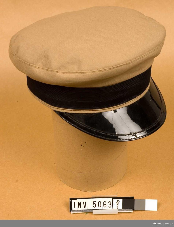 Av beigefärgat tyg med svartlackerad skärm och svart mössband.Stämpel i kullen med kronstämpeln 1970,56. 56 avser storleken på mössan.