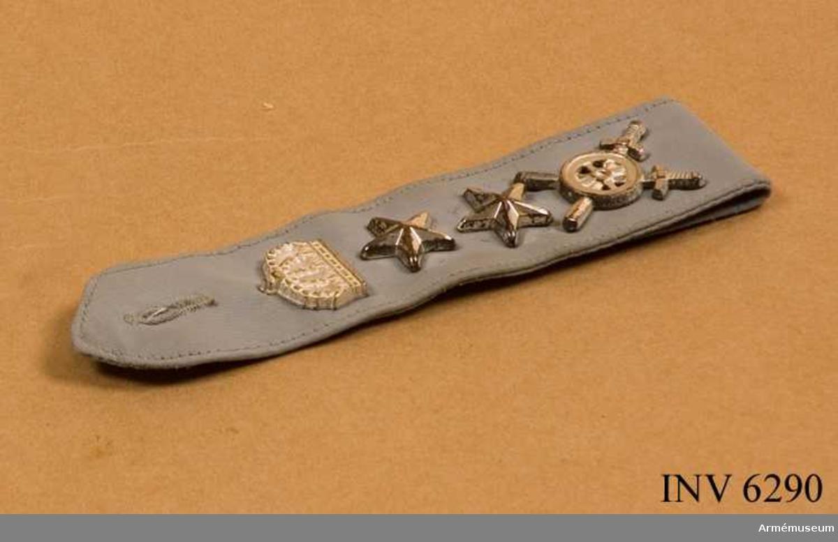 Tillverkad av gråblått syntettyg. Gradbeteckning för Överstelöjtnant i form av två stora stjärnor i silver,  trängkårens emblem och krona m/1960 (för regementsbefäl, vilket ej är Överensstämmande med en stabsredaktör). Längd dubbelvikt 145 mm. Bredd 35 mm.Tämligen gott skick.