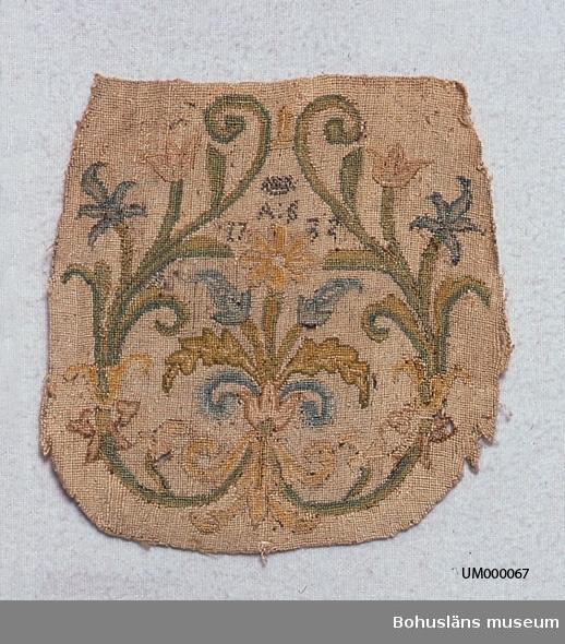 """Broderi med rak överkant och rundad underkant. Kan pga formen möjligen ha varit använt till en liten väska(?). Yttäckande broderi i petit points med silketråd; blomsterslingor som utgår från en blombukett (slingorna bildar upp och nervänd hjärtform). Märkt med metalltråd: en krona? och under den """"A:S"""" """"1732"""". Färgerna i broderiet är gulbeige botten och mönster i olika gröna, gula och blå nyanser samt ljusbrunt och ljust gultonat rött (skärt). Observera att även UM000063 från samma givare är från 1732. Givaren Johanna Selina Eding f. Strandberg f. 1801 d. 1890 var gift med Carl Fredrik Eding f. 1789 d. 1867, överstelöjtnant, sparbanksordförande. Vid deras giftermål förvärvade C.F. Eding det gamla tegelbruket på Elseberg och Elsebergs gård där de bosatte sig. Efter C.F. Eding är Edingsvägen uppkallad. Ytterligare uppgifter om givarens släktförhållanden se UM000064. Några små hål. Blekt. Trasiga kanter längs rundade sidan.  Omkatalogiserat 1997-11-21 VBT  Ur handskrivna katalogen 1957-1958: """"Silkesbroderi 1732 Mått: 14,5 x 14,5; märkt: en krona? jämte """"A:S 1732"""";  färgerna starkt blekta, trasig i kanterna.""""  Lappkatalog: 73"""