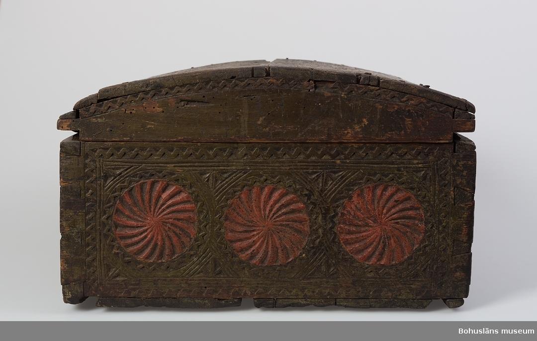 """Rektangulär med välvt lock. Tappad och sinkad konstruktion. Locket har skuren dekor i bl.a. karvsnitt och uddsnitt med virvelhjul, romber och zig-zaglinjer. Övriga sidor har också virvelhjul och zig-zagdekor. Virvelhjulen är målade med röd färg och övrig dekor i grönt. Baksidans virvelhjul är ej rödmålade. Framsidan har en fantasifullt utformad, smidd nyckelskylt. Gångjärnen är fästade på insidan locket, även de fantasifullt utformade. Insidan är rödmålad med spår av kistebrev i locket. Ett fågelhuvud och en fågelstjärt syns än idag. På höger sida finns botten till en läddika. Färgen är något sliten. Järnet har behandlats med rostskyddsmedel. Locket är något sprucket och defekt samt spikat på 1900-talet.  Litt.; Anker, Peter, Kister og skrin, C. Huitfeldts förlag A.S, Oslo, 1975, s. 65-71 samt se omslagsbilden.  Är samma föremål som UM002265.  Se Knut Adrian Andersons """"Katalog I, A. yngre föremål"""" under Uddevalla museum/förening D 2A:1 i arkivet.  Ur handskrivna katalogen 1957-1958: Träskrin,snidat, målat. L.52,5. Br. 39; H 23 cm; ett mindre fack inuti; målat i grönt och rött; karvsnitt; nyckel saknas. Mask. Ngt trasigt.  Lappkatalog: 84"""