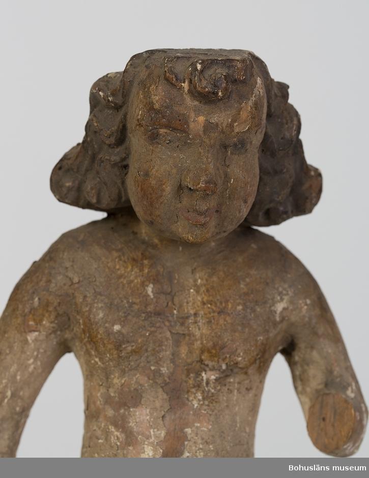 En naken gestalt (man?) som i höger hand hållit ett numera försvunnet attribut, sannolikt ett helgons pinoredskap, vänster hand saknas.  Bör ha tillhört en altartavla från 1600-talet tillsammans med skulptur UM000403 där dessa båda troligen flankerat en Kristusgestalt.  Har i tidigare katalogiseringar tolkats som Adam (UM000402) och Eva (UM000403).  Ur handskrivna katalogen 1957-1958: Kvinnobild, trä H. 29 cm; kvinnobild, naken; färgen delvis flagn. vänster arm avslagen, d. högra saknar attribut.