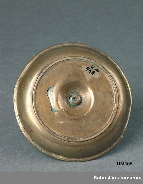 Ur handskrivna katalogen 1957-1958: Malmljusstake Diam: 11,8. H: 7,5 Koppar. Något skadad.  Lappkatalog:90