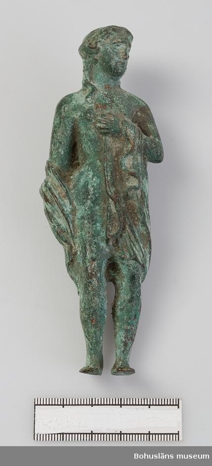 Ur handskrivna katalogen 1957-1958: Kvinnobyst av brons Pompeji. 1883-1886 H. 12,2 Br.4 Statyett. Ärgad brons. Föremålet helt. Pompeji.  Statyett i form av en kvinna med drapering runt midjan och armarnas nedre del. Föremålet har ett korrosionsskikt som täcker stora delar av figuren. Det är troligen ytterst lätt rengjort efter insamlandet. Rester av sand och jord syns i fördjupningar och mellanrum.