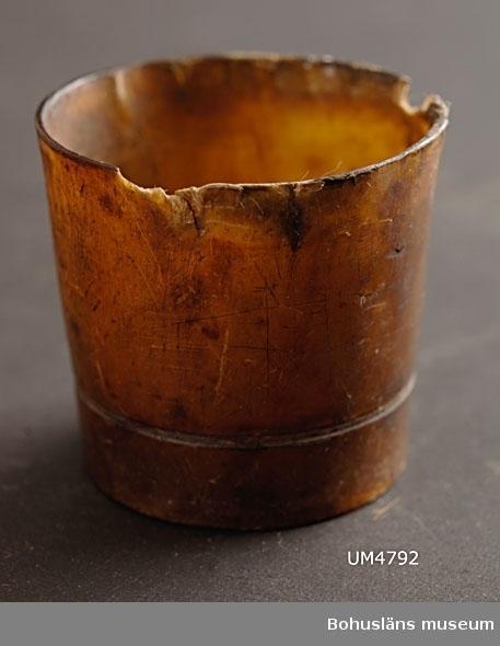 """Ur handskrivna katalogen 1957-1958: Supglas av horn H. 4,5; mynn. D. c:a 5: botten D. 4 cm; på utsidan """"1887""""; dessutom en dubbel, runtomgående linje. Ngt defekt.   Lappkatalog: 65"""