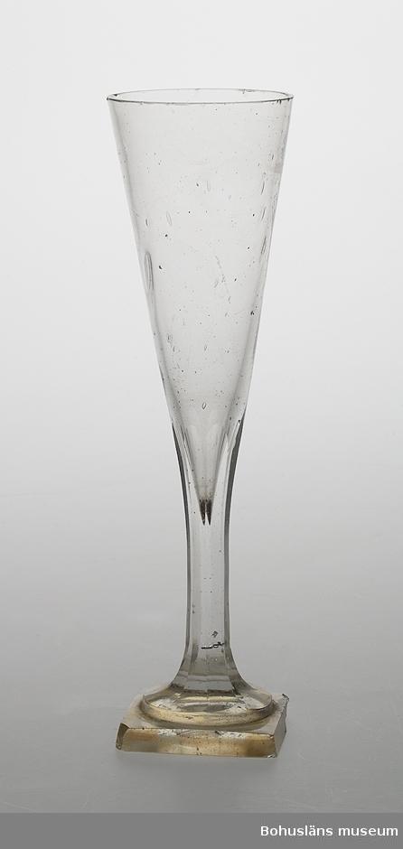 Ur handskrivna katalogen 1957-1958: Högt glas, slipad fot, utan dekoration Mynningsdiam.: 6 H: 21. Hög, smal skål, slipat skaft, fyrsidig fot. Något skadad.