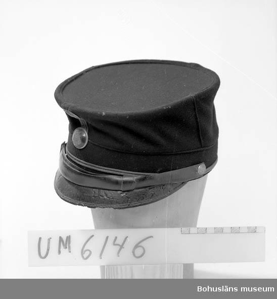 Ur handskrivna katalogen 1957-1958: Soldatmössa m/ä Mörkblå med skärm och rem av läder. Märke med Uddevalla stads vapen. Fodret trasigt.  Lappkatalog: 80
