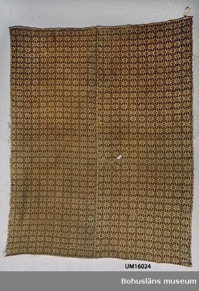 """Täcke av två våder. Ihopsytt för hand med längsgående söm på mitten. Varp och botteninslag av beige lingarn. Mönsterinslag av ljust gulgrönt entrådigt ullgarn. Helt mönstrat med stjärnor. Ena kortsidan handfållad, den andra fållen sydd med maskin troligen senare än den första. På fastnäst etikett står: """"Tillhör Gbgs o Bohusläns Hemslöjdsförening 1928 (?svårläst)"""". På etikettens andra sida står: """"53 från Bohuslän Opphämta Sprötetäcke Grönt ullgarn o ofärgat lingarn"""".  Bristningar längs båda långsidorna och i mitten av ena kortsidan. Två hål på mitten. Mönsterinslaget slitet. På baksidan är mönsterinslaget bitvis färgförändrat till gulare ton.  Litt; Berg, Kerstin, Selma Johansson - väverska och hembygdsforskare i Södra Bohuslän, Skrifter utgivna av Bohusläns museum och Bohusläns hembygdsförbund Nr 41, Uddevalla 1991, sid 178-186.  Lychou, Kerstin, Hemslöjd och folkkonst i Bohuslän, Warne förlag AB, Partille 1996, sid. 156-160.  Sekora, Ann-Britt, Upphämta i Bohuslän (uppsats vid enstaka kurs i vävning Vt 1981, Institutionen för slöjd och hushållsvetenskap, Göteborg).  För ytterligare uppgifter om givaren se UM 16001."""