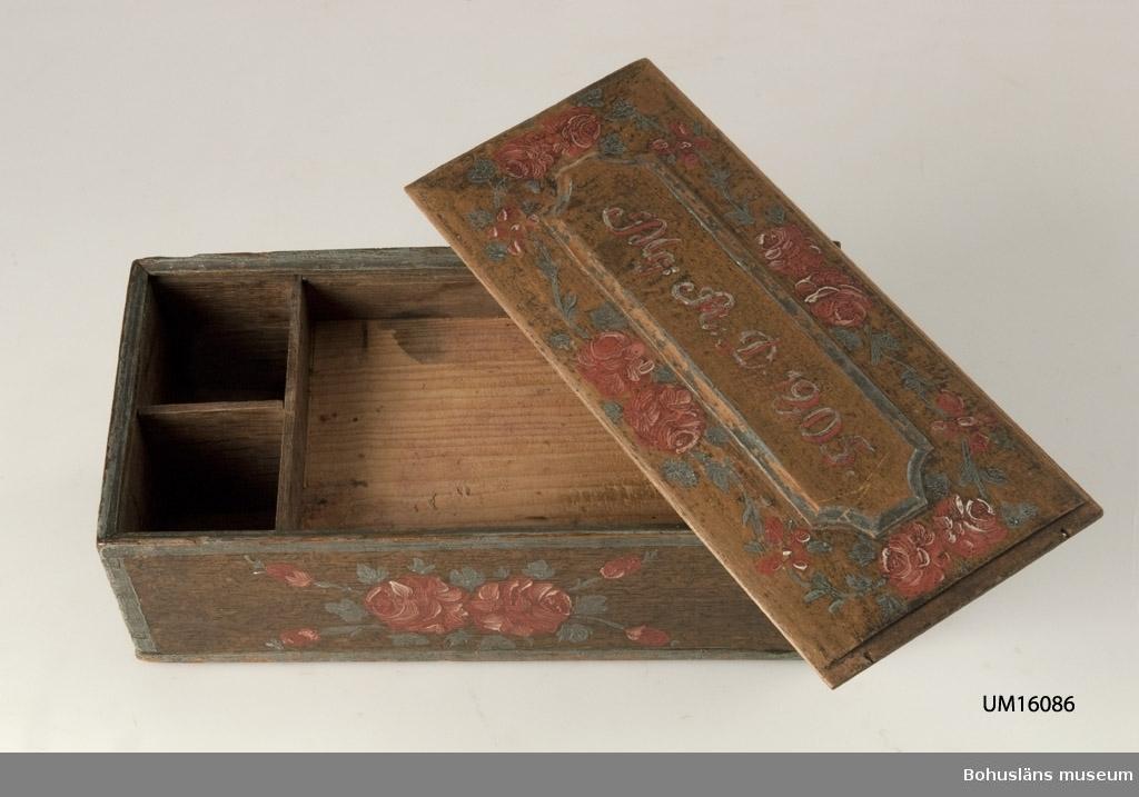 """Rektangulär med skjutlock. En profilerad list saknas på lockets ena kortsida. Ådringsmålad med röda rosor och blågröna blad på gavel och sida.  Motivet på kort- och långsida är två rosor med fyra knoppar utskjutande mot varje hörn. Runtom gavlarnas kanter löper en blå rand.  På locket röda rosor och texten: """"Mg:A.D.1805"""" i rött och vitt. Locket är något välvt med spegel i relief. Undertill finns ett hyllplan och vid en av kortsidorna är det två öppningar vertikalt. Under hyllplanet döljer sig en """"lönnlåda"""" vilken dras ut från en av kortsidorna. En rund, bred mässingsring att dra i på utsidan och inuti en rund benskiva som fäste. Under botten finns ett pappersfragment med texten; """"A. Thorén, Sund Grohed"""", troligtvis en ägare. Funktion: Förvaring."""