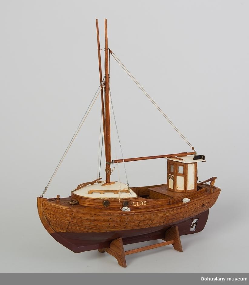"""Modell av julle med """"Britta"""", byggd på Orust som förebild.  Namnet """"Olga"""" på namnbrädan, inspirerat av Stig Selanders svärmor, som fyllde 80 år 1985, därav beteckningen LL 80. Till modellen hör fem fiskelådor,se UM016456."""