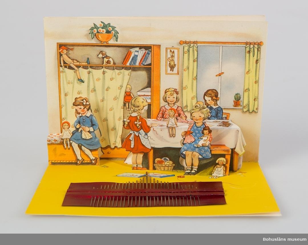 """Dubbelvikt tryckt motiv med flicka och dockor, i uppvikt form en barnkammare med från bakgrunden fristående bord och barn. Pop up-funktion. På """"golvet"""" ett nålsortiment med 29 nålar, på baksidan en nåldyna och fabriksmärke."""