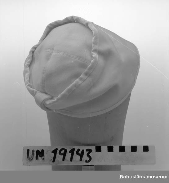 471 Tillverkningstid 1950-TAL 410 Mått/Vikt ! B.2, HJÄSSL.11 CM 394 Landskap BOHUSLÄN  Vit damhatt i mjukt bomullstyg. Sömmar klädda med ripsband.  Se UM19130.