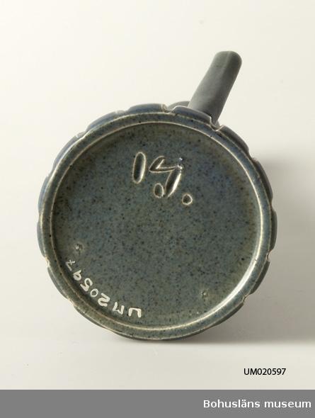 Uppåt konande vas med utsvängd mynning och med räfflad nederdel. Försedel med handtag. Inristad signatur i botten, i övrigt ingen märkning. Jfr. UM20596.