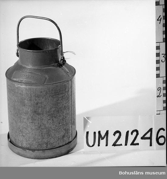 """594 Landskap BOHUSLÄN 503 Kön MAN  6-liters mjölflaska. Cylindriskt kärl med en smalare, kort hals samt rörligt bärhandtag. Nertill är det ett järnband. Mässingsskylt med instansad text: """"HASSELBERGET"""". En sexa (6) instansad vid halsen. Lock saknas. Järnbandet är löst.  Omkatalogiserat 1997-01-13 GH.  UMFF 3:12"""