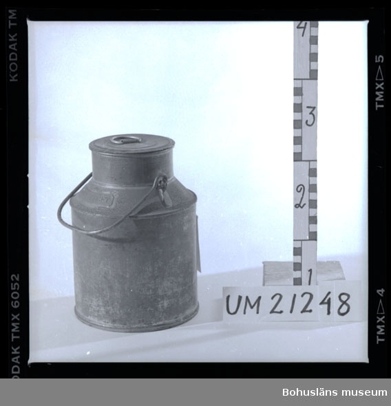 """594 Landskap BOHUSLÄN  3-liters mjölkflaska. Cylindriskt kärl med en smalare, kort hals samt rörligt bärhandtag. Lock med hänkel. Mässingsskylt med instansad text: """"HASSELBERGET"""". Det är en trea (3) instansad vid halsen. Föremålet är korroderat.  Omkatalogiserat 1997-01-14 GH.  UMFF 4:3"""