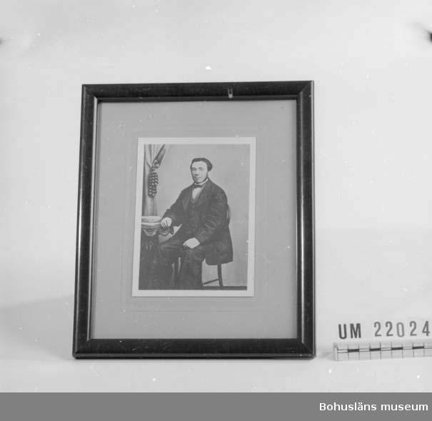 410 Mått/Vikt ! 0,28 KG, H 27,3, B 23, TJ 1,2  CM 594 Landskap BOHUSLÄN  Bilden föreställer en man i högtidskläder, taget i fotoateljémiljö. I en enkel brun ram med öglar och snöre för upphängning på baksidan.  UMFF 71:12