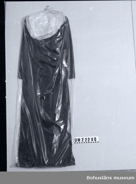 151 Sakord *NNING 594 Landskap BOHUSLÄN  Blå klänning med skärp i ryggen. Dragkedja i sidan, tryckknappar vid hals och ärmlinning, vadderade axlar. Klänningens upphängning och förvaring i plastpåsen identisk med Hasselbergets.  UMFF 98:9