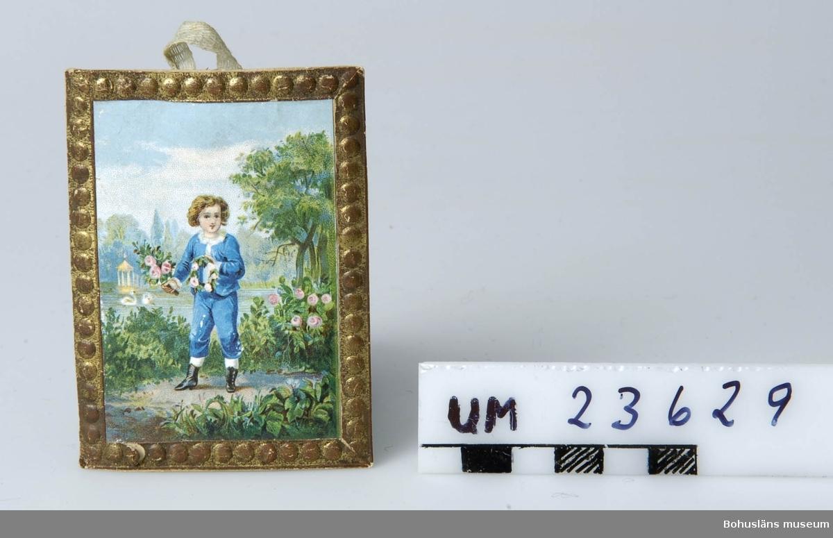 Föremålet visas i basutställningen Uddevalla genom tiderna, Bohusläns museum, Uddevalla.  594 Landskap BOHUSLÄN  Guldbromserad ram med pärlstav runtom. Bild med parkmotiv. I förgrunden liten gosse med blommor i handen. Hänkel av bomullsband.