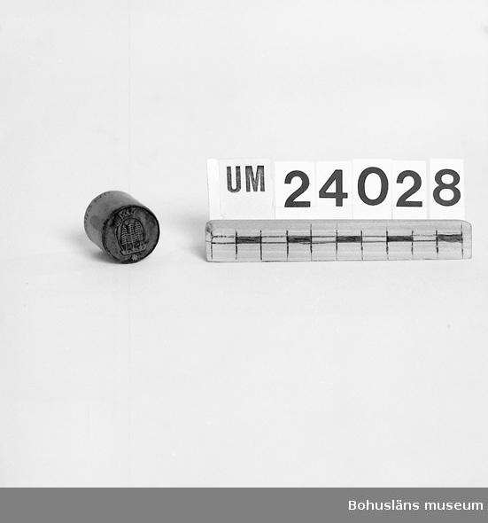 471 Tillverkningstid 1900-1950 594 Landskap BOHUSLÄN 394 Landskap BOHUSLÄN  Cylinderformad hållare på vars enda ända fastsatts metallplatta med Uddevalla vapen i relief. Använd att driva in vapnet i olika produkter