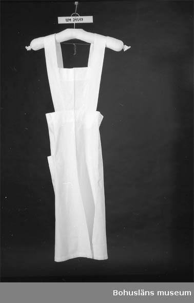 """594 Landskap BOHUSLÄN  Vitt. """"Kjol"""" med bröstlapp. Helt öppen baktill. En utanpåficka på kjolen.  På bröstlappen sitter två axelband, ca 6 cm breda, vilka knäpps fast med vita plastknappar i kjolen baktill. På insidan vid nederkanten finns två stycken vita märklappar:  1) Ceris text: """"ST J"""" 2) Röd text: """"40""""                                                  Hör ihop med UM24542 och UM24545."""