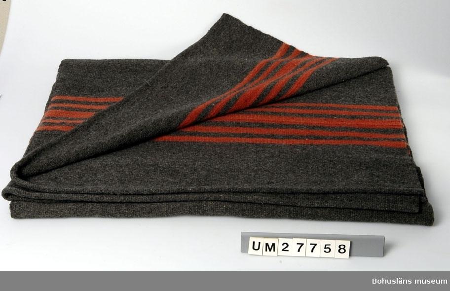 Handvävd yllefilt i inslagsrips i två våder av handspunnet entrådigt ullgarn. Ihopsydd på mitten med längsgående söm. Kortsidorna  fållade  med rullsöm. Botten av grå ulI och med kulörta dekorränder i 13 cm breda randade partier i rött i båda ändar av filten. Det grå garnet är antagligen exempel på återbruk av omspunnen ull, s.k. raffelgarner.  Filtarna är hemvävda av givarens mormor. Morfar var indelt soldat och familjen bodde på ett litet hemman som hette Vänhem och var ett soldattorp med ett par kor, grisar och några höns . Man hade inte får men det fanns i trakten. Morfaderna var borta på tjänstgöring under perioder varje år. Augusta vävde för familjens bruk. Det fanns flera målade kistor i hemmet innehållande textilier hon hade vävt. Givaren minns morföräldrarnas säng som stod högt uppbäddad om dagarna, bl a med filtar av denna typ i. Givarens fru berättar om en fjärde filt, i kulörta färger på röd botten, som mormodern också tillverkat. Denna har fått ny användning och har nyligen sprättats isär och gjorts om till soffklädsel till sommarstugan. Den var också i fint skick.