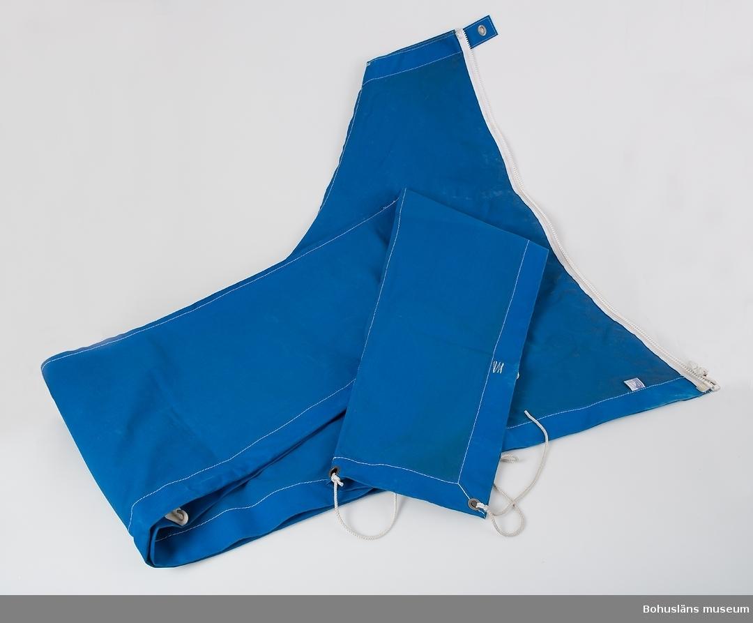 Formsytt bomkapell i blått kanvastyg med vita sticksömmar. Vid maständen med vit dragkedja av plast, knäppen av kapellknapp som fästes mot masten. Längs kapellets ena sida en infälld vit elastisk stropp som löper genom öglor, på andra sidan vita plasthakar som hakas runt linan.