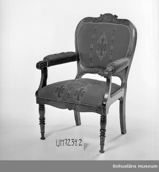 Stol stoppad sits, rygg och armlän.  Ur verksamhetsberättelse 1972 för Uddevalla museum: Några verkligt goda möbler från 1800-talets mitt, en soffa, två karmstolar, ett bord och en med pärlemor- och metallinläggningar rikt dekorerad chiffonjé, har s. a. s. återbördats till Uddevalla. Givare är fru Ida Koch, Stockholm, som därmed enligt egen utsago kunnat uppfylla sin 1953 avlidne makes, lektor Carl O. Koch, av den kända uddevallasläkten, uttalade önskan.  Möblernas ägare, Carl Olof Koch, föddes 1877 på Vågsäters gamla bruksherrgård och före detta järnbruk i Valbo-Ryrs socken i Munkedals kommun i sydvästra Dalsland. Han var son till brukspatron Carl Simson Koch (1829-1886) och Martina Elisabeth Fröding  (1836-1912).  Från 1700-talet drevs här järnmanufaktur med tegelbruk, såg - och kvarnverksamhet. Familjen Koch drev även Liljenfors bruk. Gården hade även stora åker- och skogmarker. Egendomen köptes på 1780-talet av Simzon Koch (1757-1822) och ägdes av familjen till 1877.  Simzon Koch var son till Michael Koch (1715-1789), borgmästare i Uddevalla. Simzon Koch hade tidigare drivit familjens gamla manufakturer vid Kollerö, Rådanefors och Öxnäs tillsammans med sin bror, Erik Koch och fadern under Koch & Söner. Simzon Kochs son Mikael Koch d. y.  (1792-1869) och sonsonen Carl Simzon Koch (1829-1886) drev Vågsäter vidare. 1877 förvärvades egendomen av Munkedals Aktiebolag.  Litt: Kristiansson, S: Uddevalla stads historia, del II och III. Uddevalla 1953 och 1956.