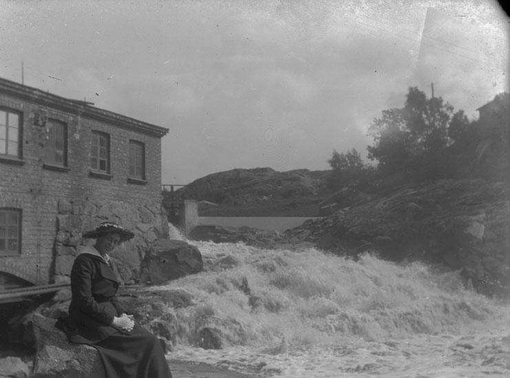 "Enl. text i blå bok: ""Dam sittande på sten vid byggnad"" ::"