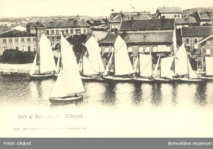 """Tryckt text på kortet: """"Strömstad. Parti af Södra Hamnen."""" """"Gust. Krügers Cigarr- & Herrekiperingsaffär."""""""