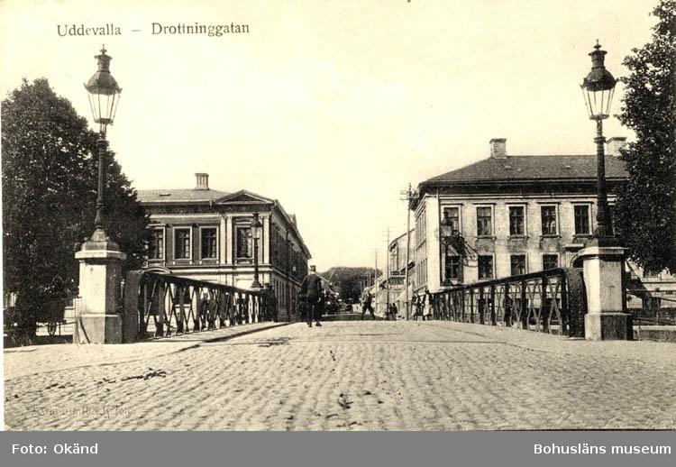 """Tryckt text på vykortets framsida: """"Uddevalla - Drottninggatan.""""  ::"""