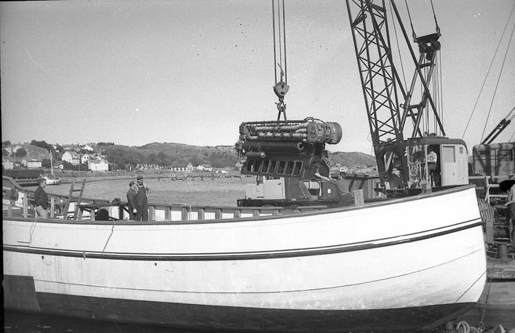 """Enligt fotografens notering: """"Skanidamotor lyfts i fiskebåt 1962""""."""