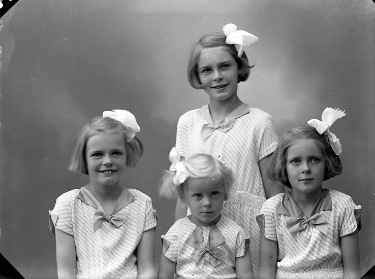 Fyra flickor med rosetter både i håret och på klänningarna