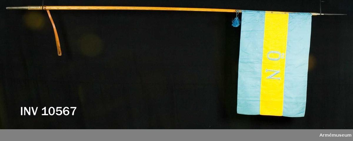 """Grupp B I.  Blå och gul flagga sydd i tre våder, varav den i mitten är gul.  Sidenflagga. Mitt på det gula mittsidenet är broderat med blått  silke """"ÖN"""". Fastsatt med silkesnodd som dragits genom kulor med hål. Inl enligt go 19510928 nr 3596.  Samhörande stång?, fodral, skyddsduk."""