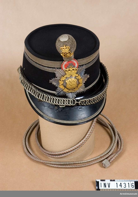 """Grupp C I. Uniform f kapten. Käppi m/1911 m pompong, 10 inf.bataljon, 7 inf.reg, Danmark. Med skärm. Runt om och botten täckt m svart kläde. Vid nedre kanten remsa, b: 20 mm, av svart läder m silversnören. Vid övre kanten två silvergaloner, övre b. 15 mm, nedre b: 10 mm. På baksidan finns en ring f att koppla snodden t käppin. Snodden av silver och röd silketråd. Foder av svart silketyg med firmastämpel """"Magasin du Nord, Köbenhavn"""". På fodret två bokstäver, initialer, av gulmetall. Svettrem av svart läder. Hakrem av svart läder m kätting och spänne av vitmetall. Remmen knäppes t käppin m knappar av vit metall. Pompong av silversilketråd i päronform och på framsidan danske konungen Kristian X:s namnchiffer av gul metall m krona ovanpå. Hållare av mässingstråd. Vapenplåt i form av sju-uddig stjärna av vit metall m krans och sköld i mitten m danska statsvapnet, tre lejon, allt av gulmetall. Ovanpå vapenplåten en rund, dansk kokard, röd och silverfärg. Litteratur: Armeen Album I, Die Daenische Armee in ihrn gegenwärtigen Uniformierung, Leipzig, Verlag von M Ruhl, sida 8-9, Infanterie,Die Offiziere: Officerarna har """"tschakå"""" m två silvergaloner (käppi), vit hakrem, pompong av silvertråd m konungens namnchiffer. Bilaga sida 3, bild i färger: Officer i paraduniform m samma käppi, utan plym, och snodd. Danske Uniformer Haer og Flaade, tegnede af Rs. Christiansen, Kövenhavn, Bild """"Oberst af fodfolket, Galladrag (i paraduniform) i samma käppi m snodden.Enl Granberg 1951."""
