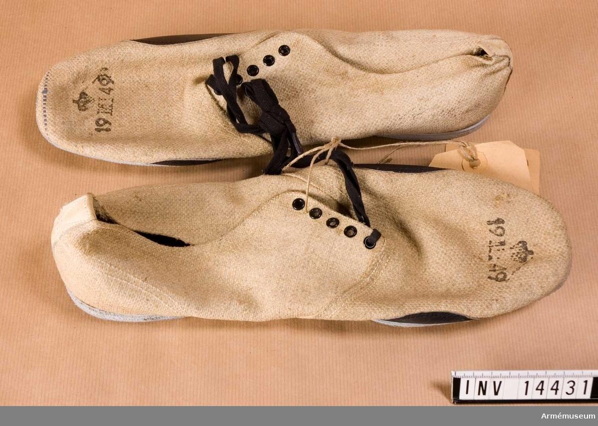 """1949. Grupp C I. Av vit lärfttyg med lädersulor, med inskärning på framsidan och försedda med fem par järnringar för att snöra skorna med snören av svart bomullsband. På skorna finns stämplar: """"19 M 1 49"""" med krona över, Munitionsdepot No 1, 1949. På sulorna finns stämplar: """"44"""", storlek och """"1430""""."""