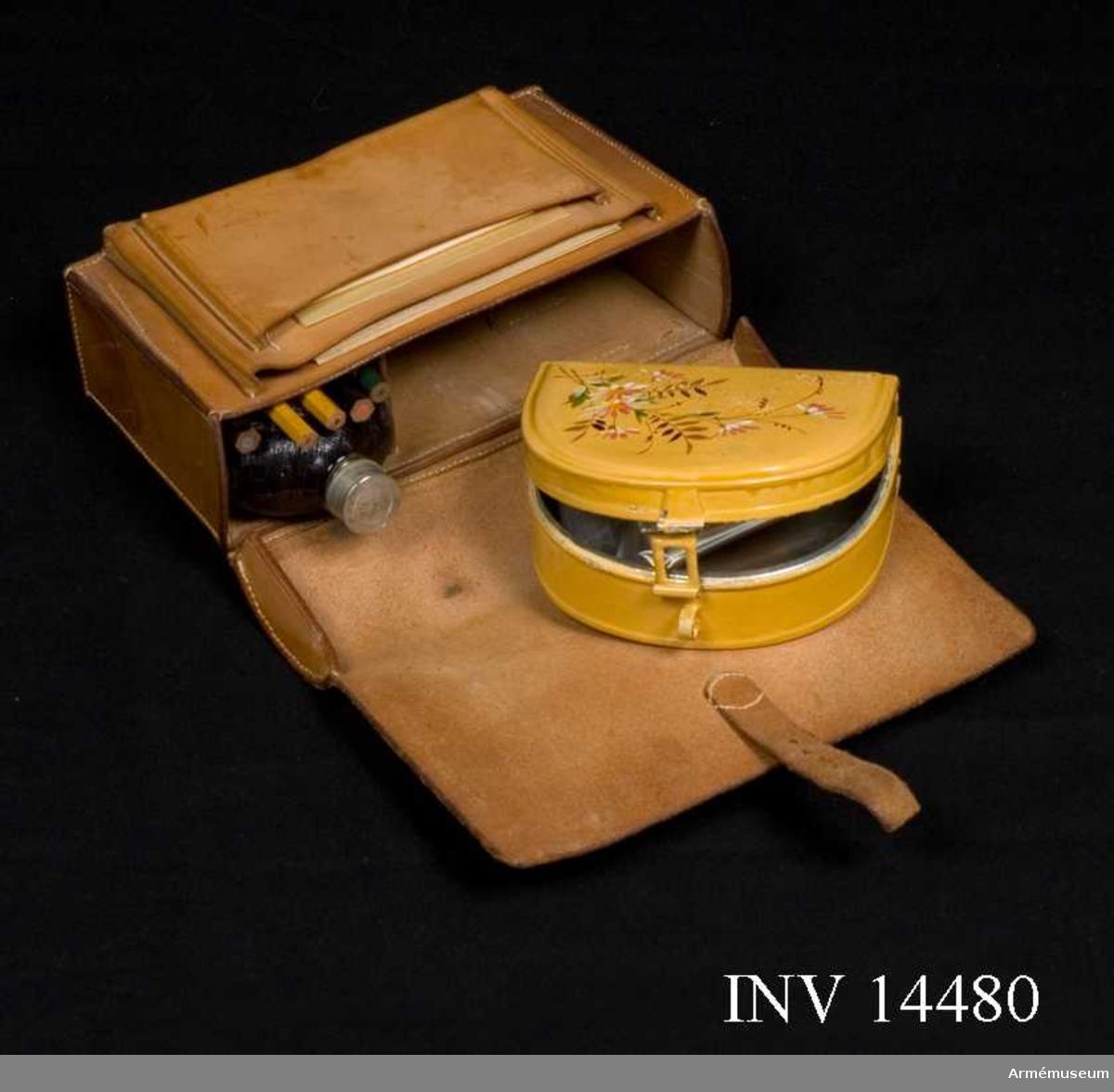 """Grupp C II Väska av naturfärgat läder. Väskan är inredd med ett fack för plåtask, ett fack för flaska och fem hållare för pennor. I väskan finns en halvcirkelformad plåtask som är målad gul på  tre sidor.  Askens lock har blommor och blad målat. Handtag av  läder. Asken innehåller rester av skorpa. Vidare finns fem blyertspennor: Två grafit (avsågade), en röd,  en grön och en blå.  Flaskans övre halva är klädd med svart skinn. På undre halvan  finns ett fodral av bleckplåt som går att ta bort. Skruvkork av plåt med en korkbit inuti. På framsidans utsida finns två fickor. I den större fickan finns  sju rapportkuvert, varav ett innehåller fyra blanketter med 8 x 12 rutor (för avstånd) på ena sidan och andra sidan har  tryckt """"Från"""", """"Till"""", """"Afgångsort:"""" och """"Den  /  kl.  m.""""  Den främre fickan har ett tunt, ganska genomskinligt papper med  fyra rutindelade fält för avstånd 0 - 5 km samt ett """"P.M. till  ledning under fälttjenstöfningarna 1899"""" - föreskrift nr 821 i go 7 juli 1899. Locket viks över hela framsidan och stänges på väskans undersida  med rem och spänne. På väskans baksida finns två 30 mm breda hällor av läder fastsydda. Mellan hällorna finns svag blyertsskrift """"Håkansson""""."""